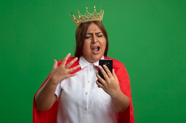 왕관을 들고 녹색에 고립 된 전화를보고 화가 중년 슈퍼 히어로 여성