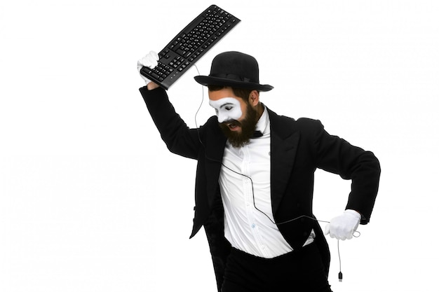 Angry mime as a businessman is destroying  keyboard