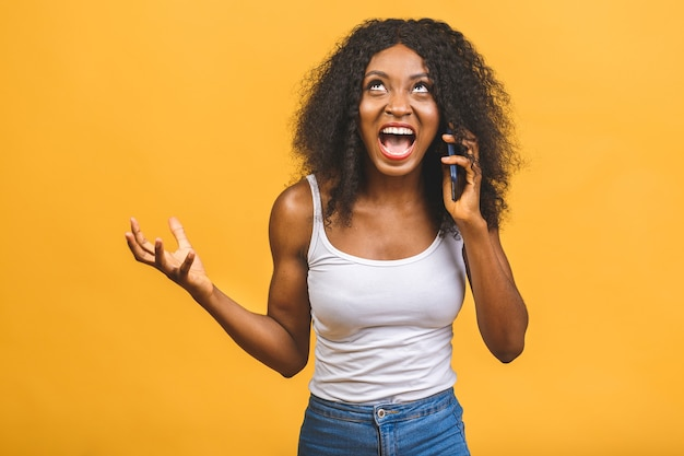 Angry mixed race black african american woman shouting in mobile phone