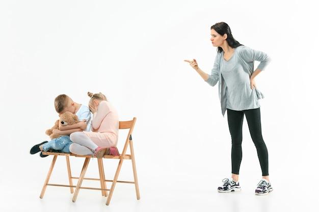 집에서 아들과 딸을 꾸짖는 화가 어머니. 감정적 인 가족의 스튜디오 샷. 인간의 감정, 어린 시절, 문제, 갈등, 가정 생활, 관계 개념