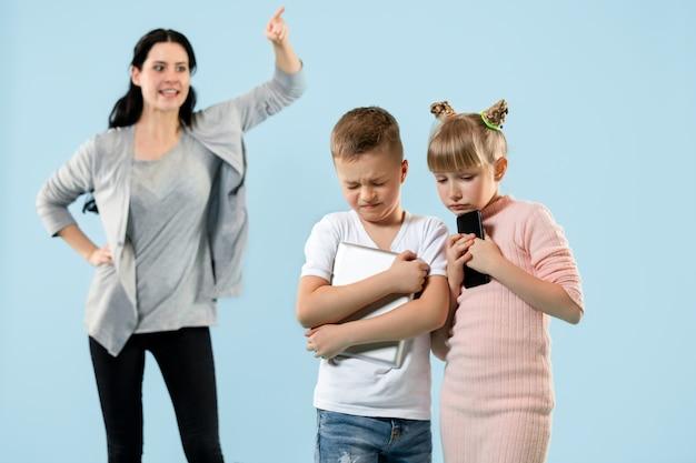 怒った母親が息子と娘を家で叱る。感情的な家族のスタジオショット。人間の感情、子供時代、問題、紛争、家庭生活、人間関係の概念
