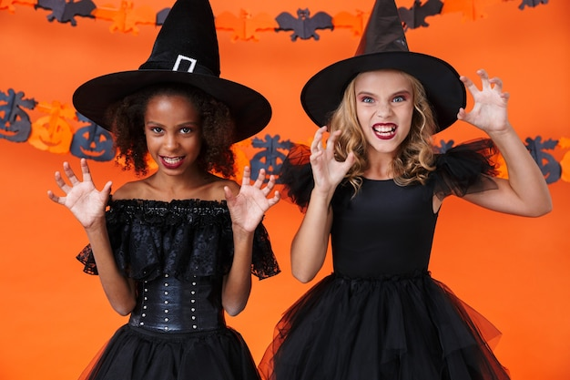 Angry multinational girls in black halloween costumes scratching and frightening isolated over orange pumpkin wall