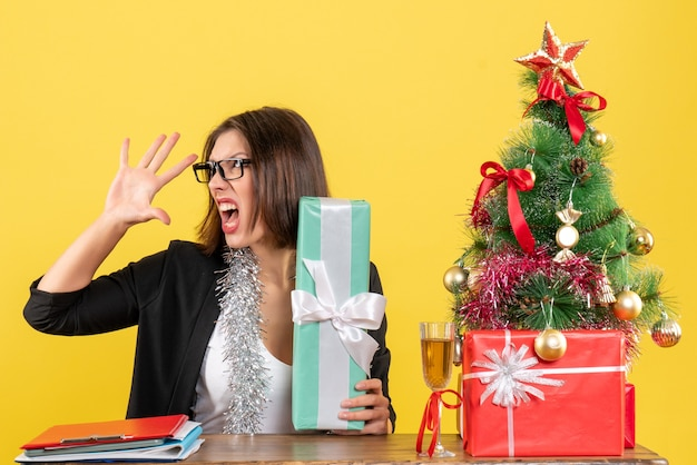 彼女の贈り物を示し、オフィスでその上にxsmasツリーとテーブルに座って眼鏡をかけてスーツを着て怒っている神経質なビジネス女性