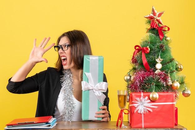 Signora nervosa arrabbiata di affari in vestito con gli occhiali che mostra il suo regalo e che si siede a un tavolo con un albero di natale su di esso in ufficio