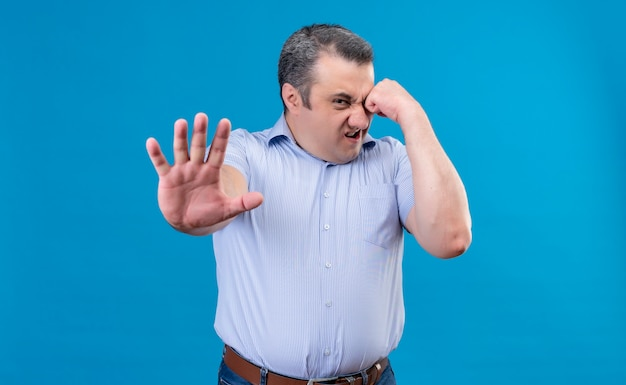 Angry and nervous middle-aged man in blue shirt showing stop gesture with hands on a blue space