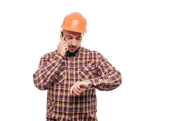 An angry and nervous worker in an orange helmet is talking loudly on the phone, shouting into the phone. isolated white background