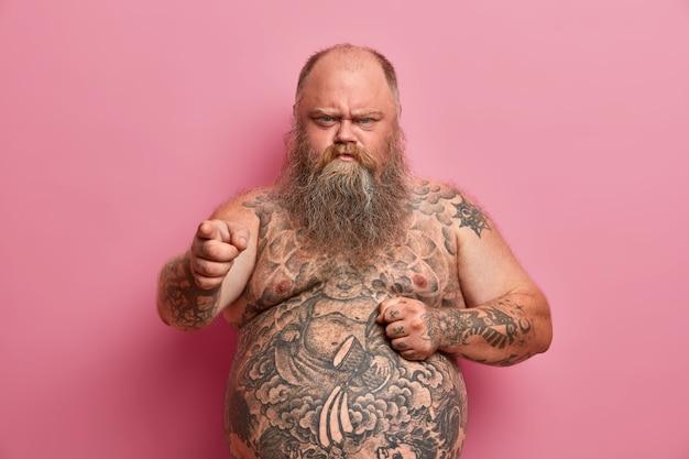 L'uomo arrabbiato e offeso in sovrappeso tiene la mano sulla grande pancia nuda e ti incolpa, sente parole offensive su se stesso, ha un corpo tatuato e una barba lunga e folta, tenuto a dieta