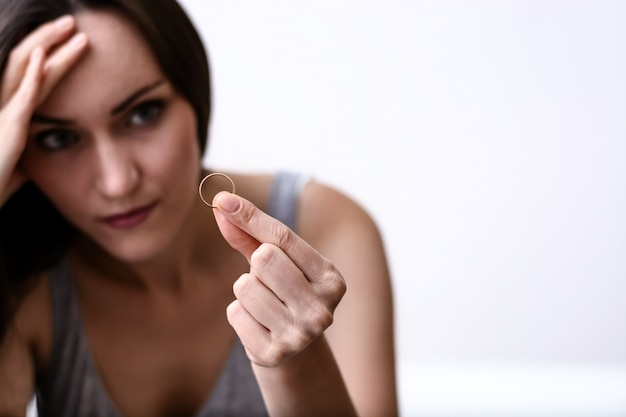 Angry and offended wife depressed after divorce, holding with hand a wedding ring sitting on a room floor.
