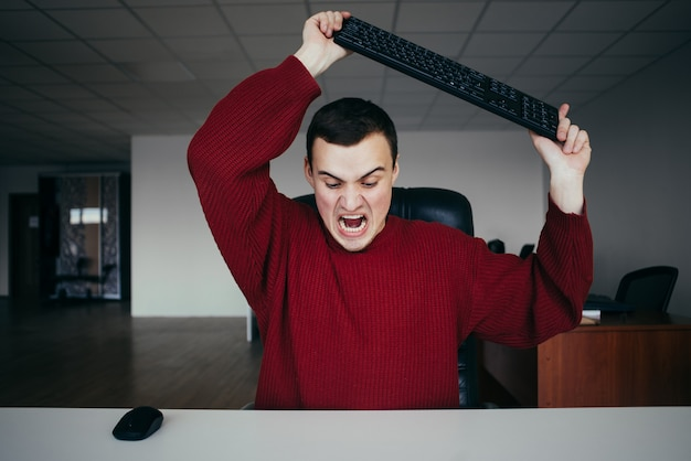 Angry office worker about to smash your keyboard. the situation in the office. a young man with a keyboard in his hands