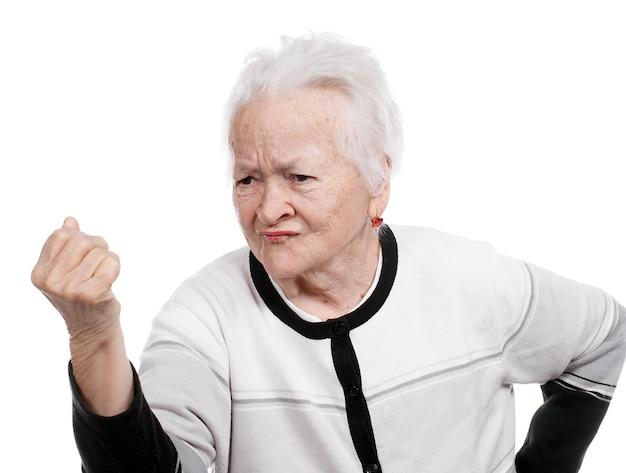 Сердитая старуха, сжимая кулак изолированы