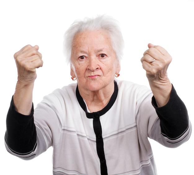 Сердитая старуха делает изолированные кулаки