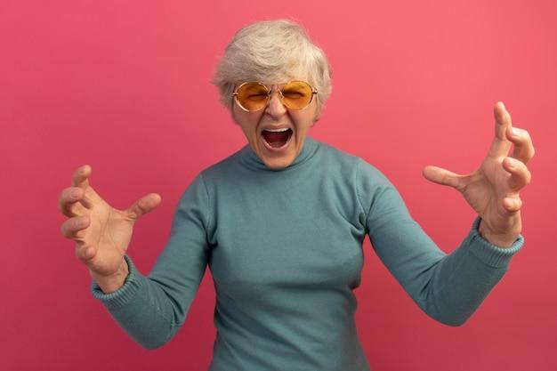 青いタートルネックのセーターとサングラスを身に着けている怒っている老婆は目を閉じて叫んで手を空中に保ちます
