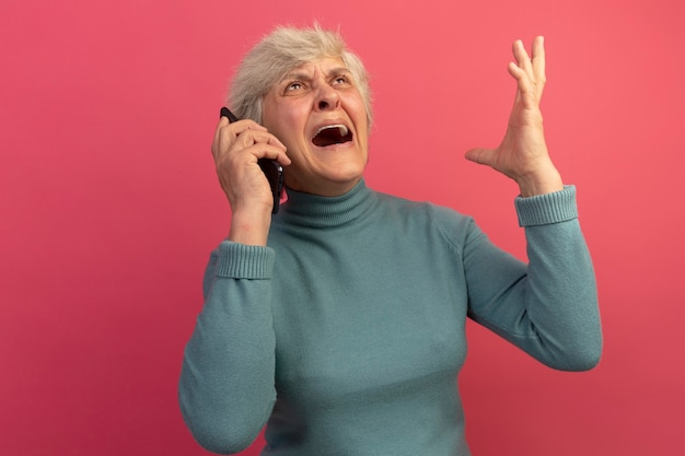 Angry old woman wearing blue turtleneck sweater talking on phone looking up raising hand up isolated on pink wall