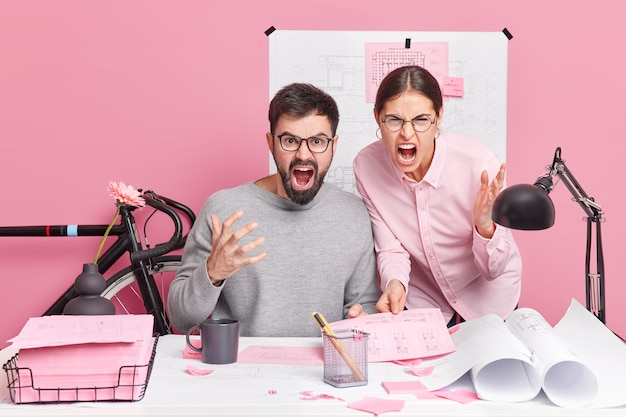 Angry outraged professional woman and man colleagues scream loudly being annoyed with difficult task pose at desktop surrounded by blueprints papers sketches collaborate for common building project