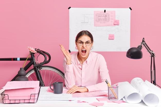 La giovane donna europea arrabbiata e indignata urla con l'espressione indignata alza il palmo esprime emozioni negative commesse errore in pose creative di schizzo sul desktop carte arrotolate e adesivi intorno