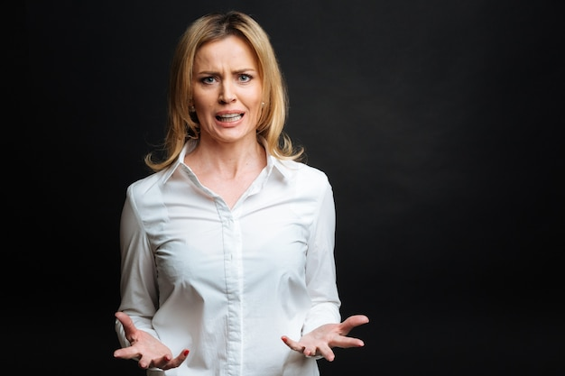 Angry overwhelmed mature woman expressing annoyance while gesticulating wildly and standing isolated in black wall