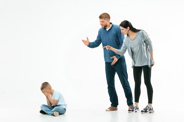 집에서 아들을 꾸짖는 화가 난 부모. 감정적 인 가족의 스튜디오 샷. 인간의 감정, 어린 시절, 문제, 갈등, 가정 생활, 관계 개념