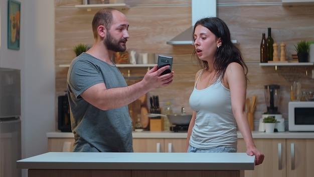 메시지에 대한 설명을 묻는 화난 파트너. 질투하는 남자는 스마트폰에서 찍은 사진으로 그녀에게 말다툼을 하며 필사적으로 비명을 지르는 외도를 하고 있다.