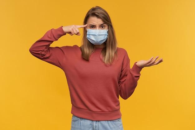 Giovane donna pensierosa arrabbiata nella mascherina facciale fredda di influenza di protezione medica che indica il suo copyspace del tempiale sulla palma sopra la parete gialla