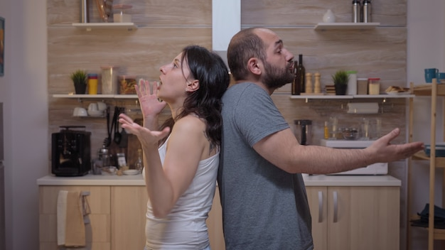 Angry people arguing standing back to back. furious, irritated, frustrated, jealous unhappy couple screaming accusing to each other having family conflict disputing sitting in the kitchen.