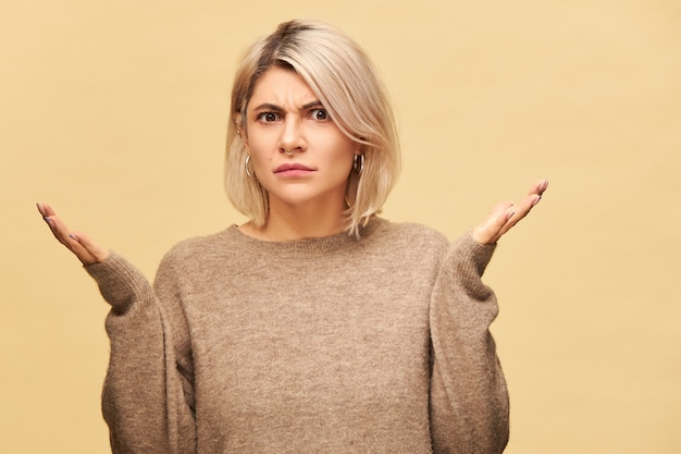 Angry perplexed young blonde woman in beige sweater frowning having indignated look, shrugging shoulders trying to figure out what happened, gesturing emotionally. blaming, warning, accusing concept