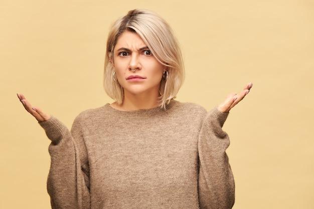 憤慨した表情で眉をひそめているベージュのセーターを着た怒っている困惑した若いブロンドの女性は、何が起こったのかを理解しようと肩をすくめ、感情的に身振りで示します。非難、警告、非難の概念