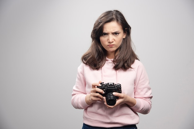 Angry photographer holding camera on gray wall.