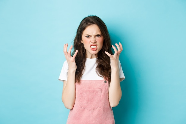 Angry and pissed-off brunette woman shaking hands and frowning outraged, look with hatred, standing furious and aggressive against blue background.
