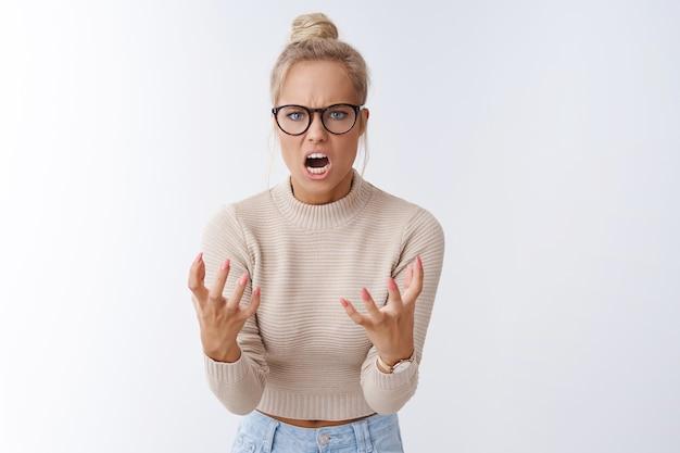 Злая рассерженная женщина, кричащая с презрением и ненавистью в камеру, сжимая кулаки, гнев, хмурясь, ведет себя в ярости и безумие, имея аргумент, который надоедает и раздражает в плохом настроении на белом фоне
