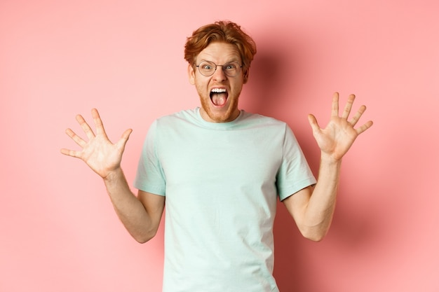 Angry and pressured young man losing temper, spread hands sideways and screaming with furious face, standing in glasses and t-shirt against pink background.