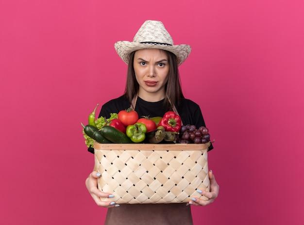 野菜のバスケットを保持しているガーデニング帽子をかぶって怒っているかなり白人女性の庭師
