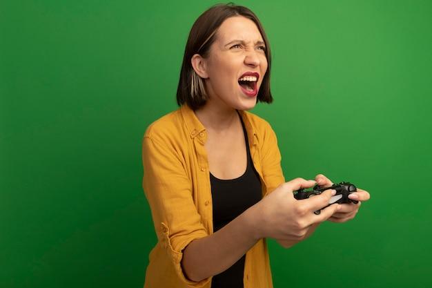 La donna abbastanza caucasica arrabbiata tiene il controller e guarda a lato sul verde