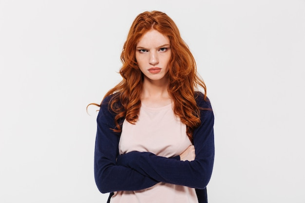 Angry pretty young redhead lady with arms crossed.