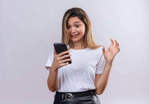 Una donna abbastanza giovane arrabbiata in maglietta bianca che esamina il telefono cellulare