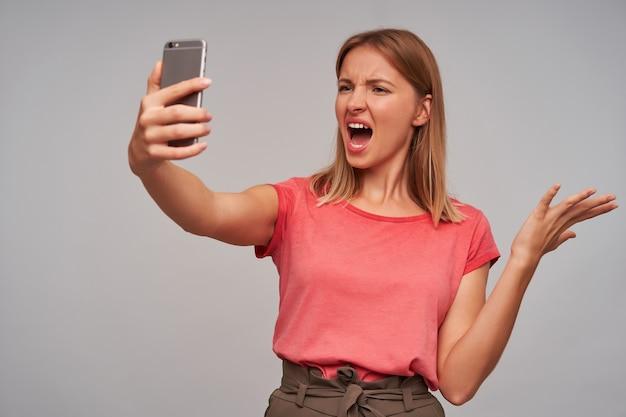 短いブロンドの髪の怒っているかなり若い女性は、携帯電話を上げた手に保ち、ビデオ通話を興奮させ、大きな口を開けてカメラを見て、眉を眉をひそめています