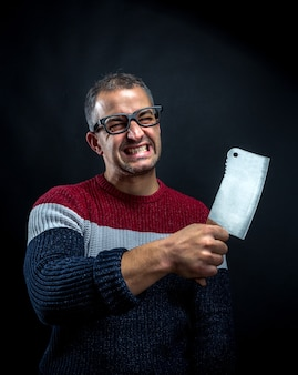 Angry psycho man in pullover with meat cleaver. crazy upset man waiting for his boss
