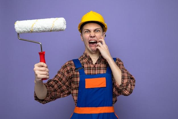 Arrabbiato mettendo la mano sulla guancia giovane costruttore maschio che indossa l'uniforme tenendo la spazzola a rullo