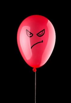 黒に分離された怒っている赤い風船