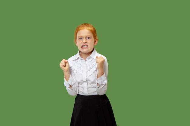 Злая рыжая девушка стоит на модной зеленой стене