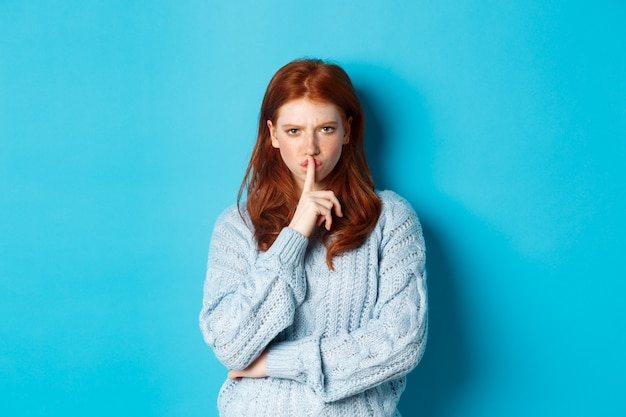 Злая рыжая девушка замолкает на вас, показывает запретный жест, запрещает говорить, стоя на синем фоне в свитере.
