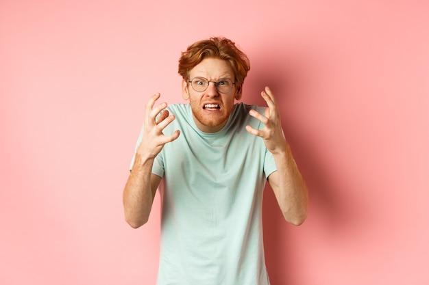 ピンクの背景の上に立って、欲求不満と憤慨した顔で叫び、眉をひそめ、握手する眼鏡の怒っている赤毛の男。