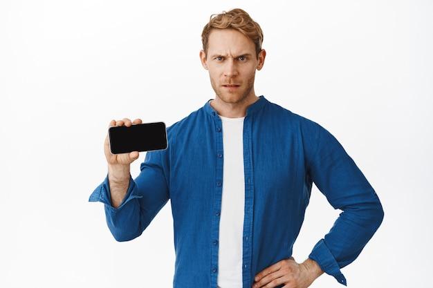 L'uomo rosso arrabbiato mostra lo schermo orizzontale dello smartphone e il giudizio accigliato, mostrando qualcosa di brutto e deludente sul display del telefono cellulare, in piedi sul muro bianco