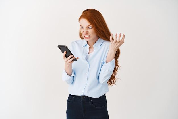 怒っている赤毛の女友達がスマートフォンの画面に腹を立てて憤慨し、憤慨し、怒りの手を握りしめ、電話、白い壁を見つめている