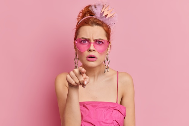 Angry redhead young woman wears stylish sunglasses and dress indicates directly  with annoyed face expression sees something stunning isolated over pink wall. monochrome shot. hey you