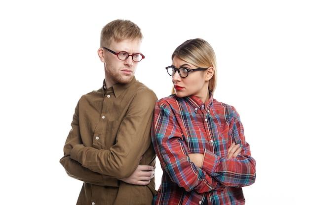 Сердитая упрямая молодая блондинка и небритый мужчина в очках стоят спиной к спине со скрещенными руками и смотрят друг на друга через плечи с серьезным недовольством.