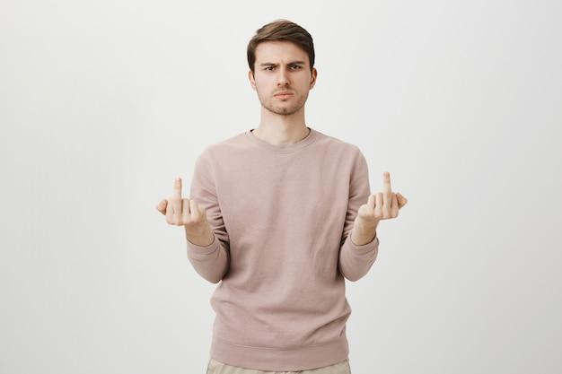 Злой грубый парень показывает средние пальцы