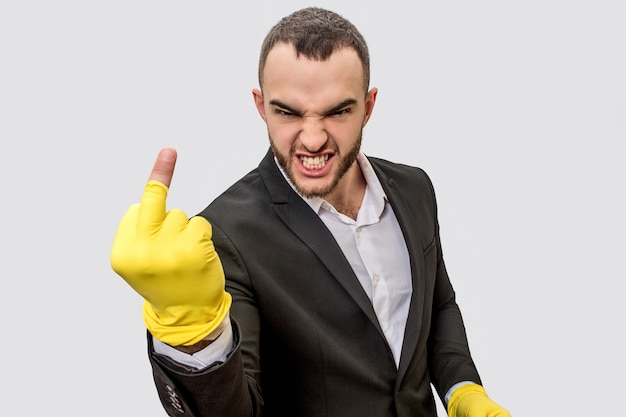 Angry and rude young man in suit stands and look on camera. he shows fuck. his hands are in yellow gloves. glove on middle finger is wrapped up.