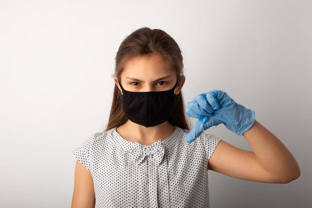Злая школьница в медицинской маске показывает палец вниз