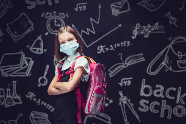 Злая школьница в защитной маске готовится пойти в школу защиты от вирусов для детей