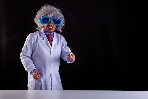 Злой учитель естествознания в белом халате с взлохмаченными волосами, в забавных очках держит палочку, чтобы указать на доску